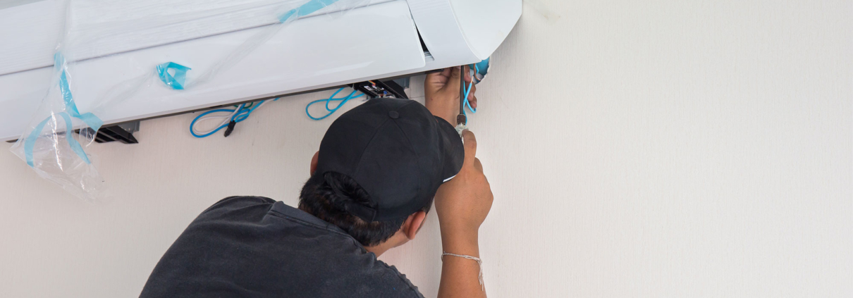 JohnΓÇÖs Service and Sales man installing air unit in home