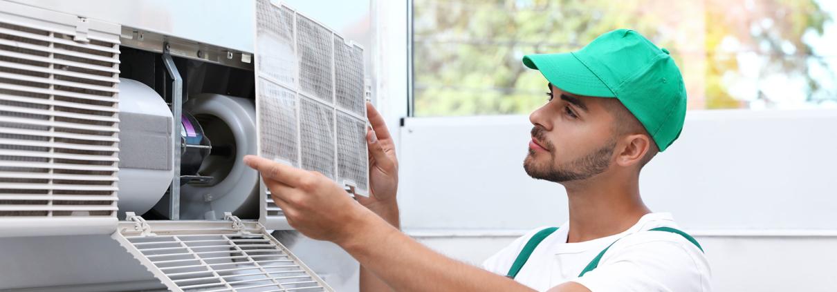 JohnΓÇÖs Service and Sales man working on air unit